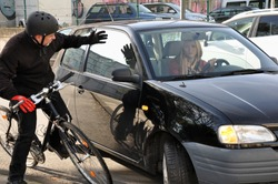 Female car driver puts a cyclist in a dangerous situation near the accident in traffic