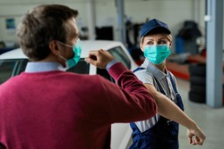 Female car mechanic and her customer greeting with elbows while wearing protective face masks in auto repair shop during coronavirus epidemic.