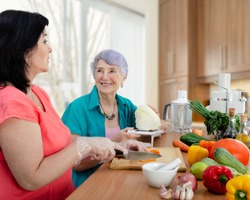 Female caregiver or volunteer and senior adult woman cook vegetable salad together. The old lady looks happy.
