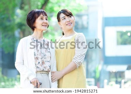 Female caregiver taking a walk with a senior woman Stockfoto ©
