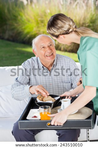 Female caretaker serving breakfast to senior man at nursing home
