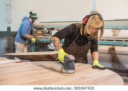 Female carpenter Using Electric Sander for wood