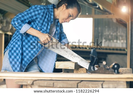Female carpenter with hacksaw, sawing the boards in the workshop