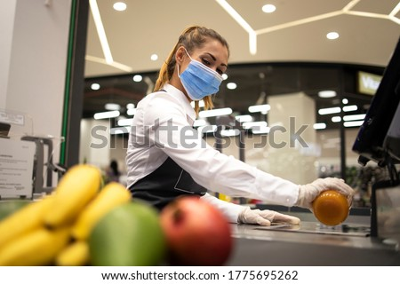 Female cashier in supermarket wearing hygienic protection mask and gloves while working risky job because of corona virus pandemic. Healthcare protection against covid-19. Foto d'archivio ©