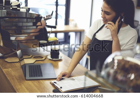Female cashier with good mood making finance report at end in working day while talking with friends on modern smartphone about meeting after job standing near coffee machine at bar with modern laptop