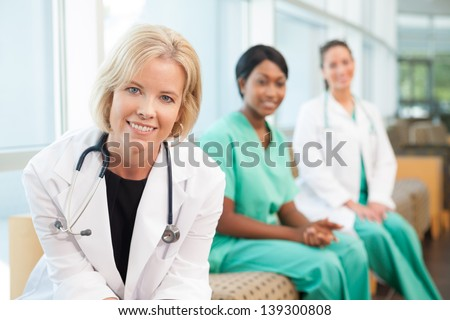 Female caucasian doctor sitting on couch with African-American nurse and hispanic nurse in hospital waiting area or lobby
