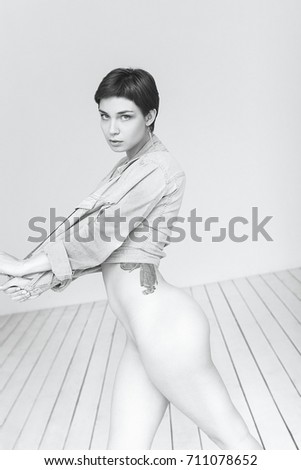 Stock Photo female Caucasian model girl tattoo attractive sexy nude short hair wooden floor white studio background posing sensual pretty jacket jeans