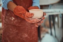 Female ceramic artist in gloves holding handmade clay bowl