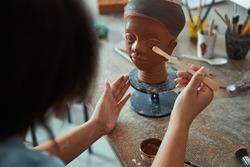 Female ceramic artist working with clay sculpture in workshop