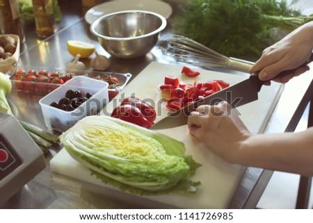 Female chef cutting vegetables in restaurant kitchen #1141726985