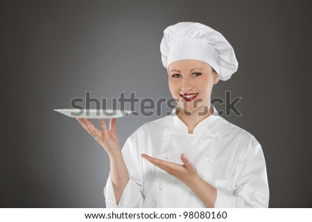 Female chef holding empty plate