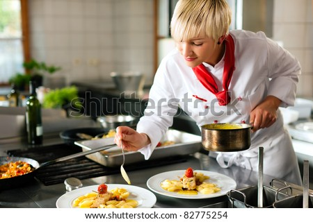 Female chef in a restaurant or hotel kitchen cooking delicious food, she is decorating the dishes