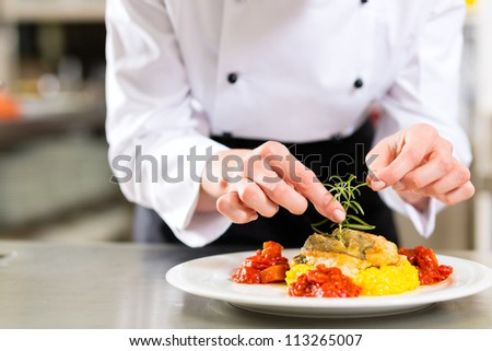 Female Chef in hotel or restaurant kitchen cooking only hands she is finishing a dish on plate