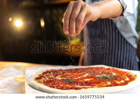 Female chef is sprinkling fresh oregano over a traditionally made home pizza.  Stock photo ©