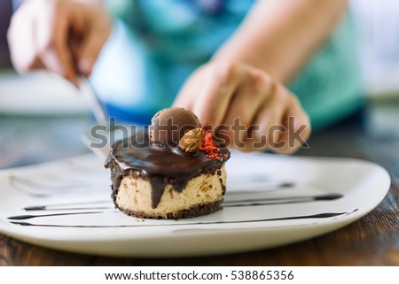 Female chef lays out a cake on a plate, dessert presentation. Dessert decorated cookies and almonds.