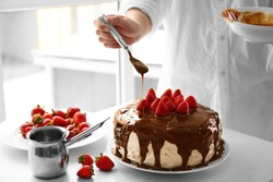 Female chef making caramel cake with strawberries