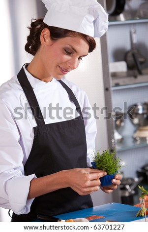 Female chef picking some garnish to use as decoration on her amuse