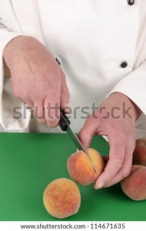 female chef preparing a peach with a kitchen knife