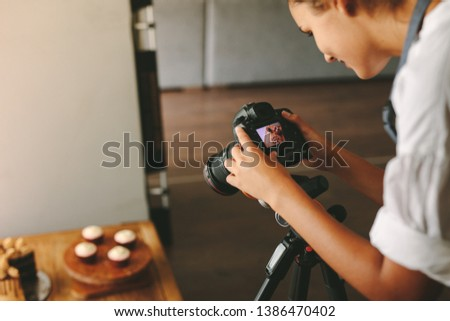 Female chef taking photos for her food blog with digital camera in the kitchen. Food photographer using digital camera to take a photo of dessert.
