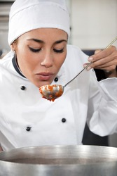 female chef tasting tomato sauce. Copy space