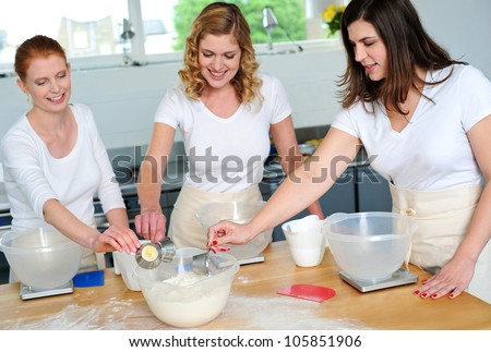 Female chefs team collecting flour from bowl for preparing something