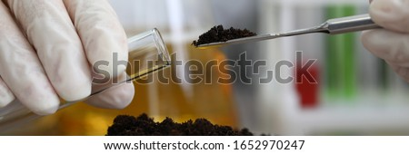 Female chemist in white protective gloves hold test tube against chemistry lab background closeup. Express research crop soil content of beneficial and harmful substances concept Photo stock ©