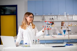 Female chemist with safety goggles hold molecular model in the lab