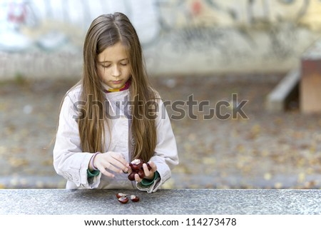 Female child collecting chestnuts. - stock photo