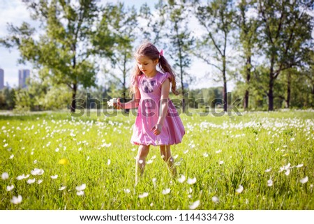 female child in a pink summer dress collects flowers in a clearing