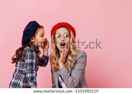 Female child tells secret to adult surprised woman. Photo of mother and daughter in checkered jackets and multi-colored berets