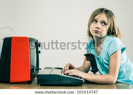 Female child typing on vintage keyboard, looking bored, with video game joystick and TV
