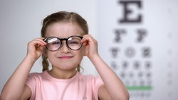 Female child with poor eyesight happy to wear comfortable eyeglasses, smile