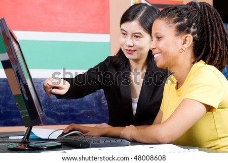 female chinese teacher teaching computer to african student