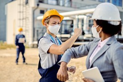 Female civil engineer and building contractor greeting with elbow while wearing protective face masks at construction site.