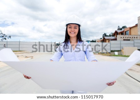 Female civil engineer looking at a house blueprints