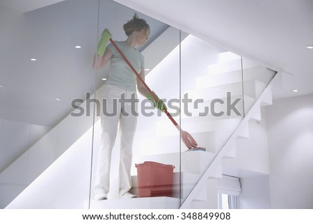 Female cleaner works in a modern home / office environment mopping the stairs
