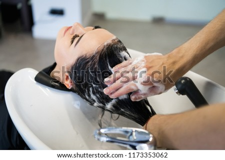 Female client getting hair washed by hairstylist in parlor #1173353062