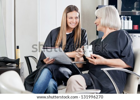 Female client's with magazine and cup conversing at beauty parlor