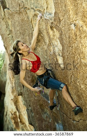 Female climber clinging to an overhanging rock face in Joshua Tree National Park.