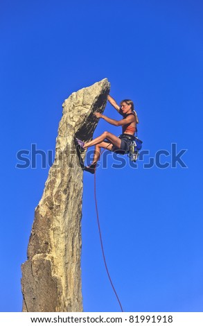 Female climber struggles up the edge of a challenging cliff.