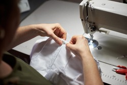 Female clothier stitching with her hands on workplace in atelier. Draping process with steel needle. Sewing machine, scissors on background. Handicraft, mastery, garment production concept. Top view
