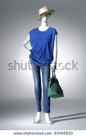 Female clothing on a mannequin in a hat with handbag on light background - stock photo