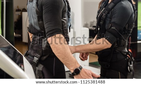 Female coach helping man with putting electro muscular stimulation suit on #1125381488