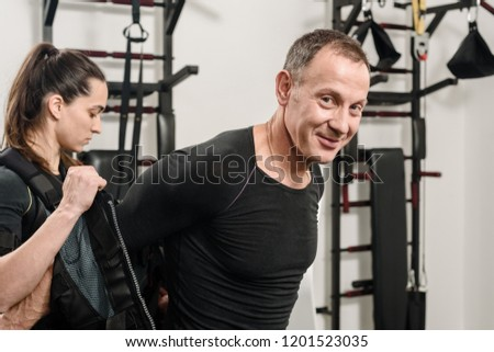 Female coach helping man with putting electro muscular stimulation suit on #1201523035