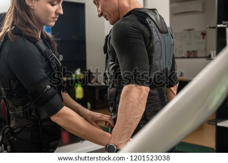 Female coach helping man with putting electro muscular stimulation suit on #1201523038
