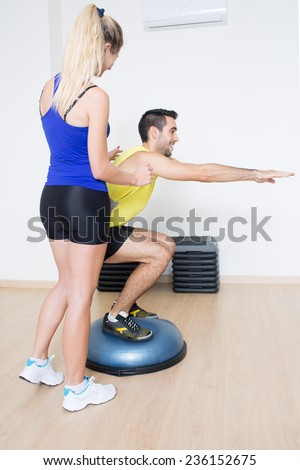 Female coach helps with a squat exercise