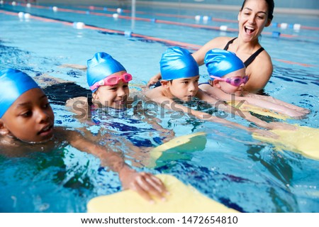 Photo of  Female Coach In Water Giving Group Of Children Swimming Lesson In Indoor Pool