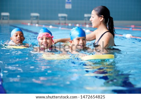 Female Coach In Water Giving Group Of Children Swimming Lesson In Indoor Pool Foto stock ©