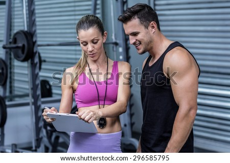 Female coach showing results to an athlete at the crossfit gym