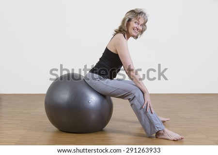 female coach shows exercise using a pilates ball